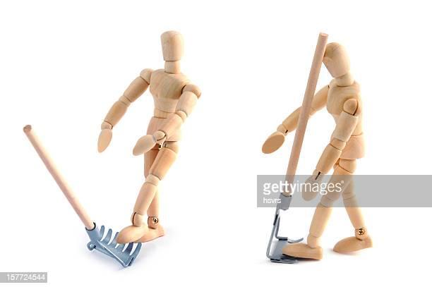 Wooden mannequin having accident of work with garden fork