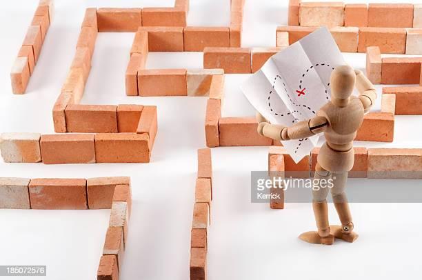 Hölzerne Schaufensterpuppe Im labyrinth mit Karte