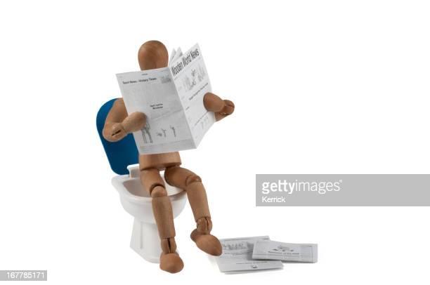 Hölzerne Kleiderpuppe auf Bad liest Zeitung