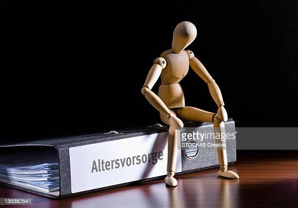 Wooden mannequin sitting on file folder