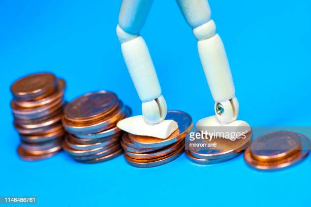 wooden mannequin with money, symbolic image for wealth - dolly golden stock pictures, royalty-free photos & images