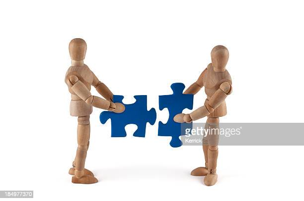 Wooden mannequins putting puzzle together