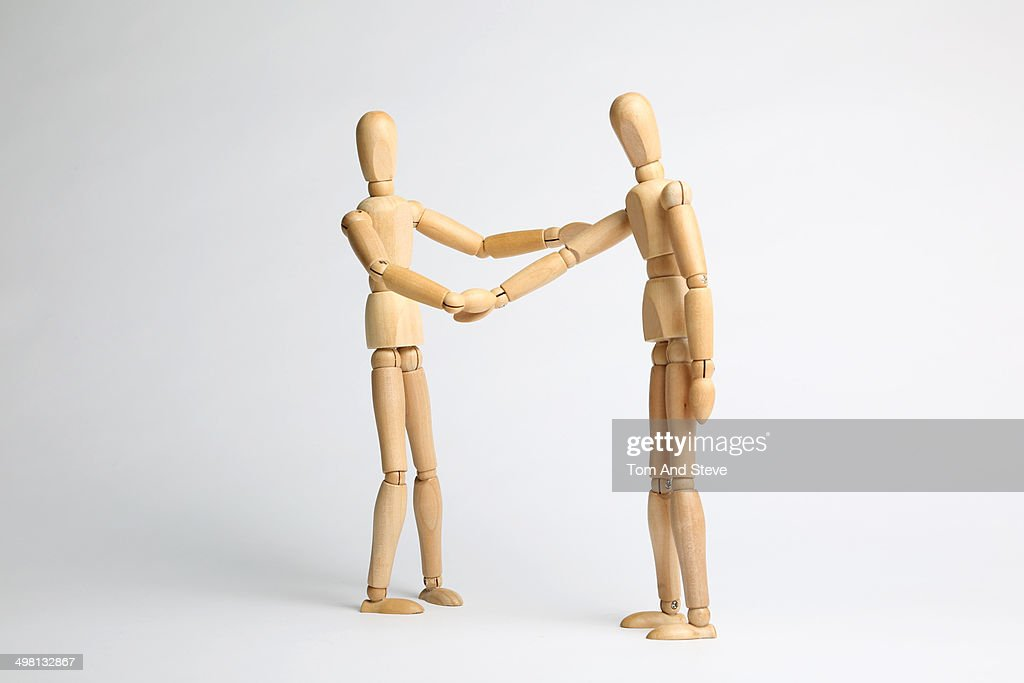 Wooden mannequins shaking hands : Stock Photo
