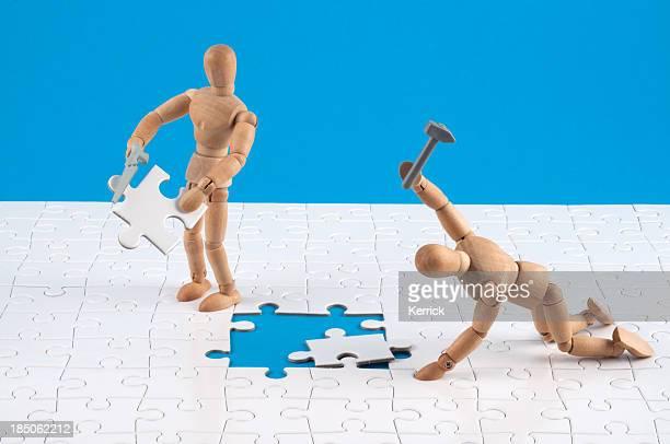 wooden mannequins working hard at a jigsaw. - oops stockfoto's en -beelden