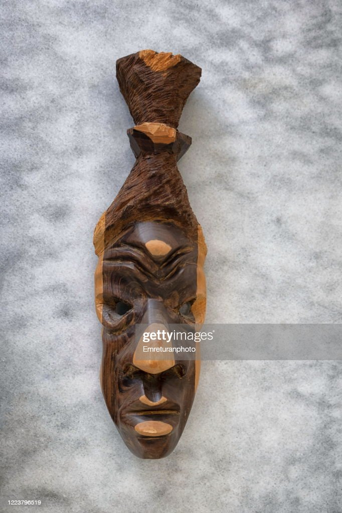 Wooden mask in two colors on gray marble tabletop. : Stock Photo