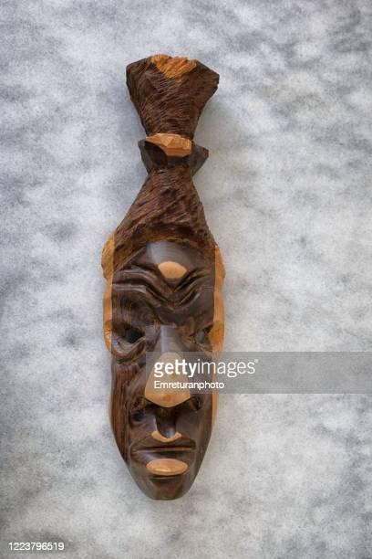 wooden mask in two colors on gray marble tabletop. - emreturanphoto stockfoto's en -beelden