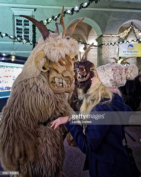 A wooden mask wearing person bewitches a visitor of the Christmas Market during the Christmas Devil Run at Domplatz on December 21 2016 in Salzburg...