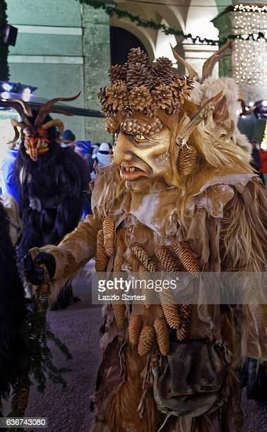 Wooden mask wearing person walks during the Christmas Devil Run at Domplatz on December 21, 2016 in Salzburg, Austria.