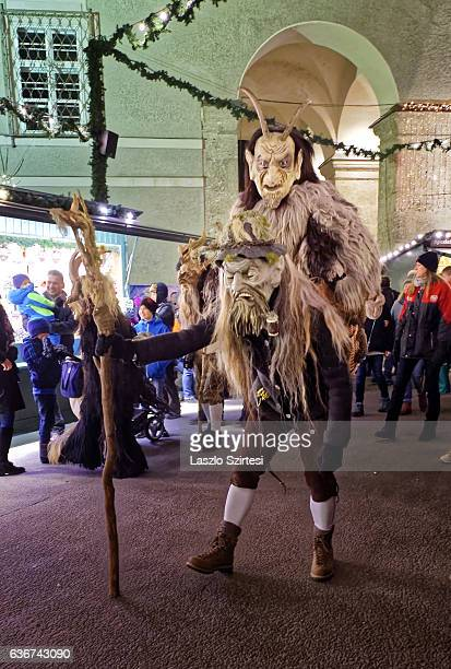 Wooden mask wearing persons walk during the Christmas Devil Run at Domplatz on December 21, 2016 in Salzburg, Austria.
