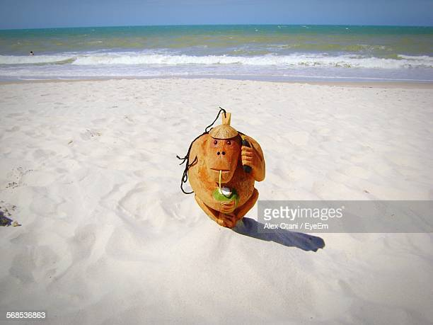 Wooden Monkey Sculpture Drinking Coconut Water While Using Telephone On Beach