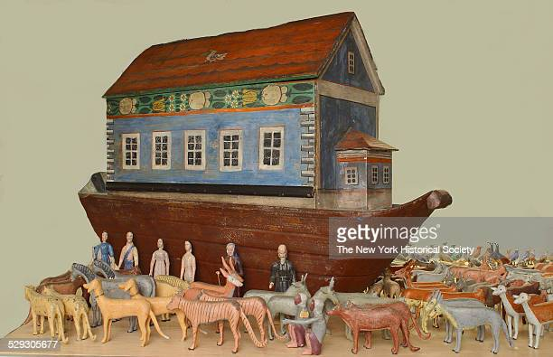 Wooden Noah's ark brown painted hull surmounted by building with peaked roof and sliding side building painted with blue walls red roof and features...
