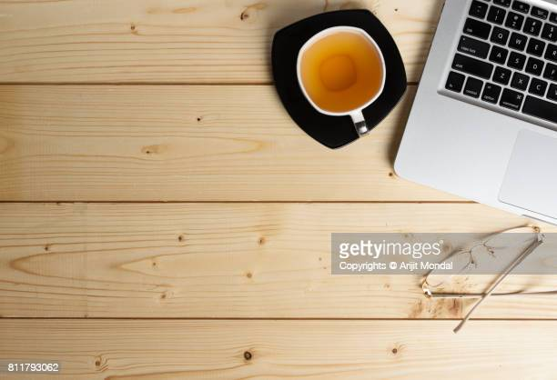 Wooden Office Table Top View with Copy Space, Green Tea, Laptop Keyboard and Spectacle
