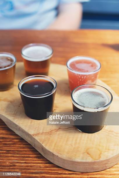 a wooden paddle with 6 craft beer sample glasses - help:ipa stock pictures, royalty-free photos & images