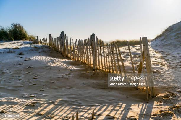 A Wooden Picket Fence Along A Beach
