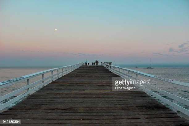wooden pier against pastel sky - medium group of people stock pictures, royalty-free photos & images