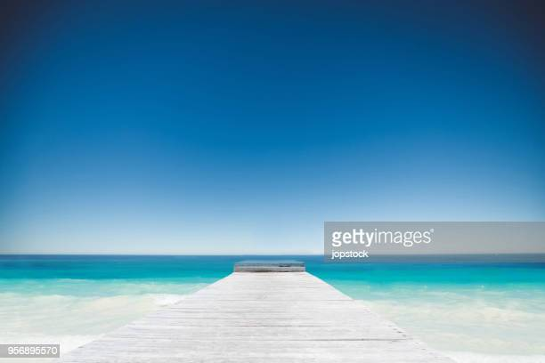 wooden pier and caribbean sea in cancun, mexico - caribbean culture stock pictures, royalty-free photos & images