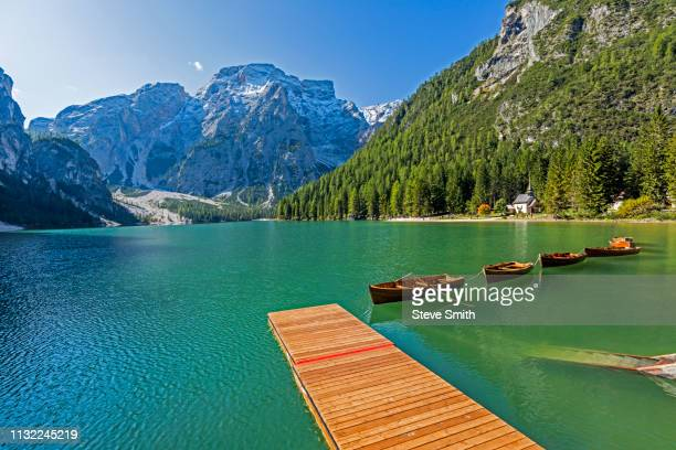 wooden pier and row boats on pragser wildsee in south tyrol, italy - pragser wildsee stock pictures, royalty-free photos & images