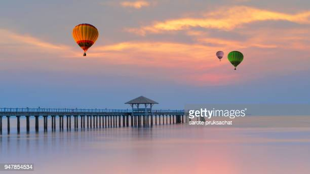 Wooden pier between sunset and Colorful hot air balloon on sunset sky in Thailand.