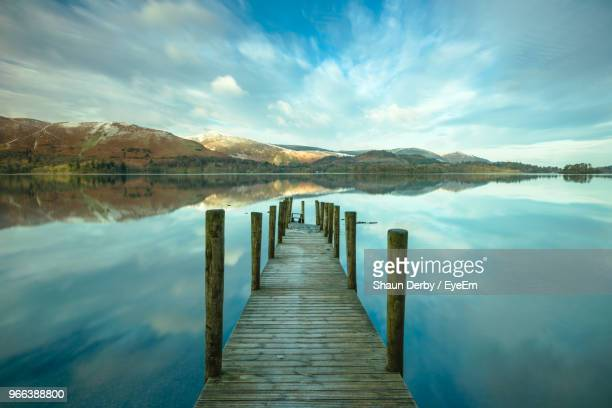 wooden pier in lake against sky - keswick stock photos and pictures