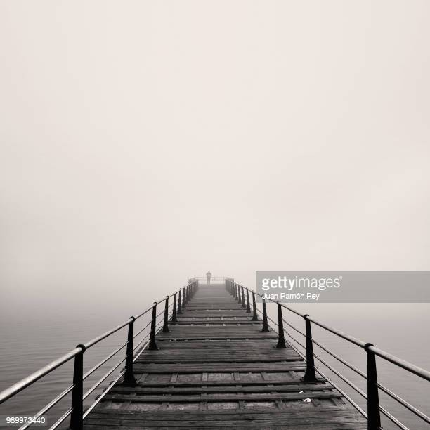 A wooden pier in the fog.