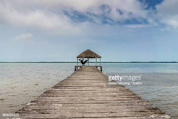 Wooden Pier Leading To Calm Sea Against Sky