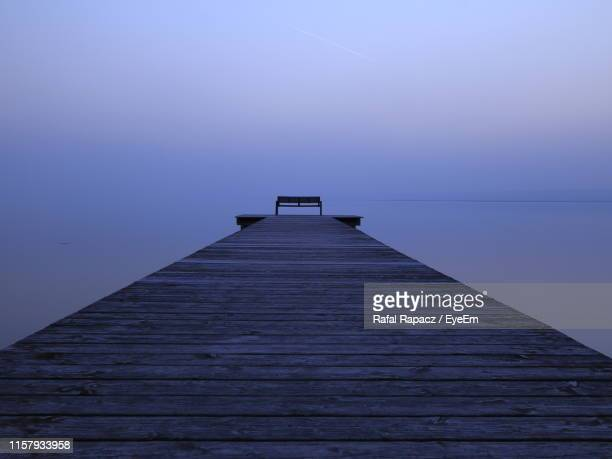 wooden pier on sea against sky during sunset - jetty stock pictures, royalty-free photos & images