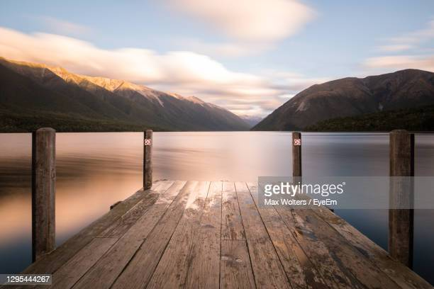 wooden pier over lake against sky during sunset - jetty stock pictures, royalty-free photos & images