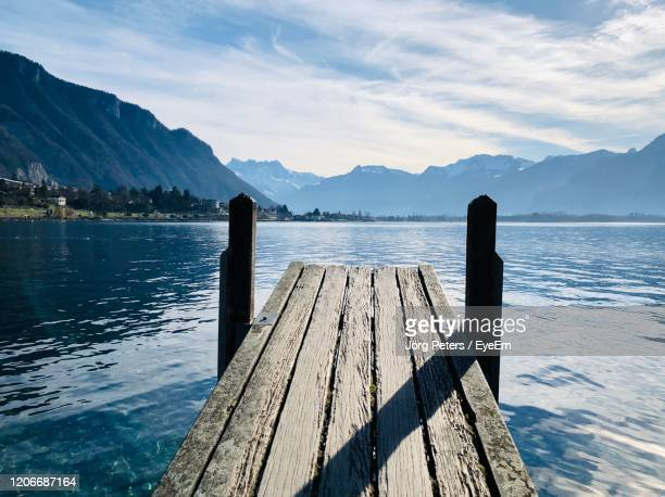 "wooden pier over lake against sky - ""jörg peters"" stock-fotos und bilder"