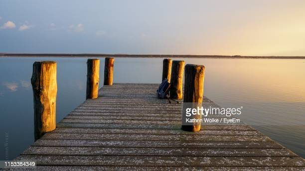 wooden pier over sea against sky - wolke stock pictures, royalty-free photos & images
