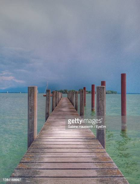 wooden pier over sea against sky - sabine hauswirth stock pictures, royalty-free photos & images