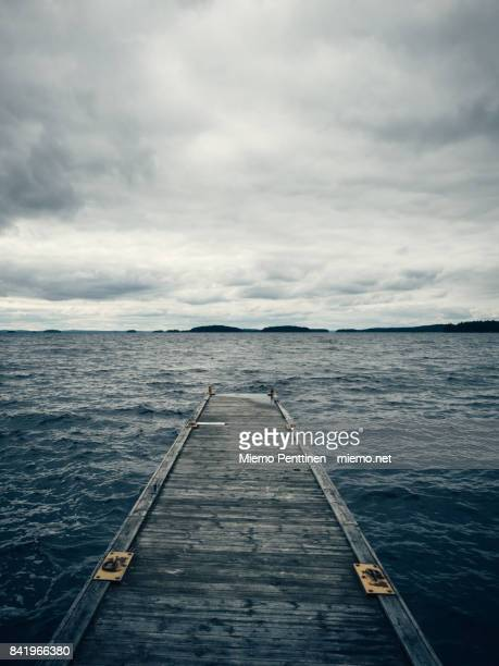 A wooden pier reaching out to lake Päijänne in Finland on a stormy, overcast summer day