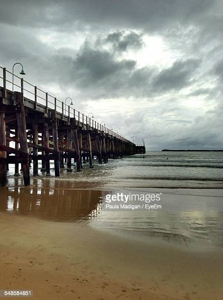 Wooden Pier Seen From Sandy Beach