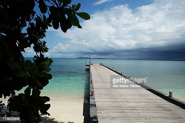 wooden pier stretching out into ocean with clouds in background - calm before the storm stock pictures, royalty-free photos & images