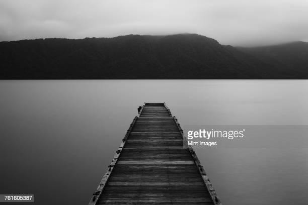 Wooden pier stretching out into the water at Towada Lake with mountains in the distance.