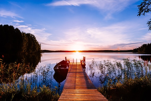 Wooden pier with fishing boat at sunset on a lake in Finland 1138147004