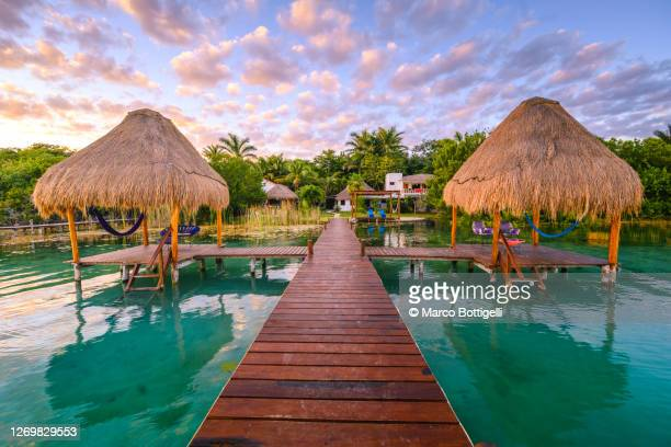 wooden pier with palapas in a tropical tourist resort - tourist resort stock pictures, royalty-free photos & images