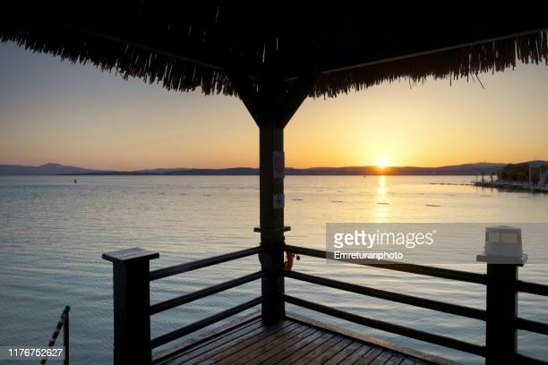 wooden pier with straw roof at sunrise in aegean coastline. - emreturanphoto stock pictures, royalty-free photos & images