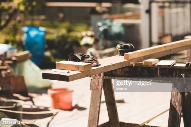 wooden planks and gloves in yard during sunny day - doe het zelven stockfoto's en -beelden