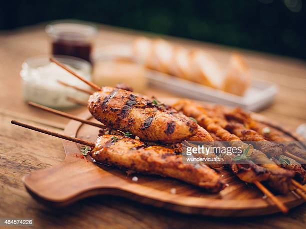 Wooden platter of barbecued bacon twists and chicken