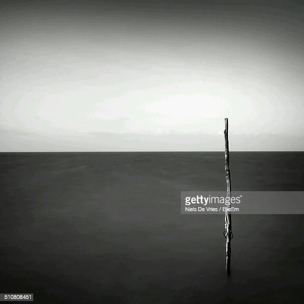 Wooden pole in sea against sky