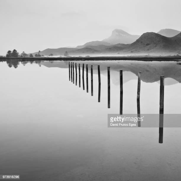 wooden poles and mountains reflecting in sea, calblanque, murcia, spain - murcia - fotografias e filmes do acervo