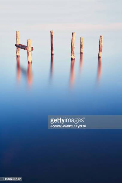 wooden poles in the water with long exposure - pole stock pictures, royalty-free photos & images