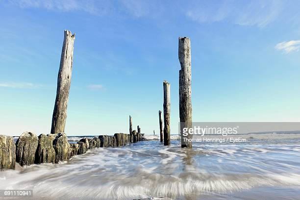 Wooden Poles On Sea Against Blue Sky