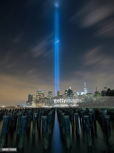 wooden post in east river against light beams symbolizing world trade center in city against sky at night - world trade center memorial stock pictures, royalty-free photos & images