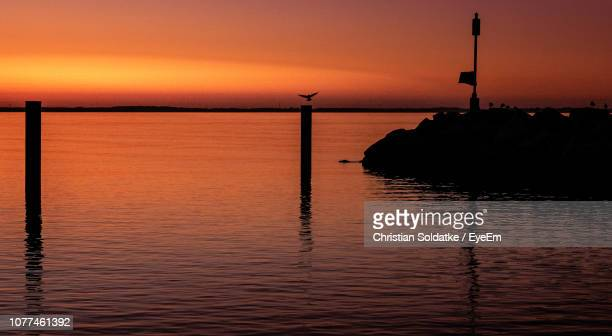 wooden post in sea against sky during sunset - christian soldatke foto e immagini stock