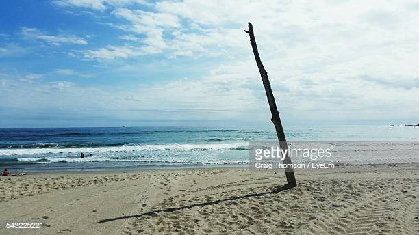 Wooden Post On Beach Against Cloudy Sky
