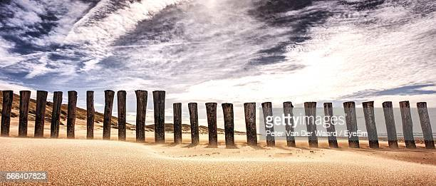 Wooden Post On Beach Against Sky