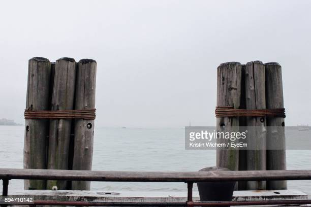 Wooden Post On Pier Over Sea Against Sky