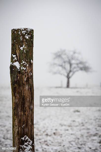 Wooden Post On Snow Covered Field Against Sky