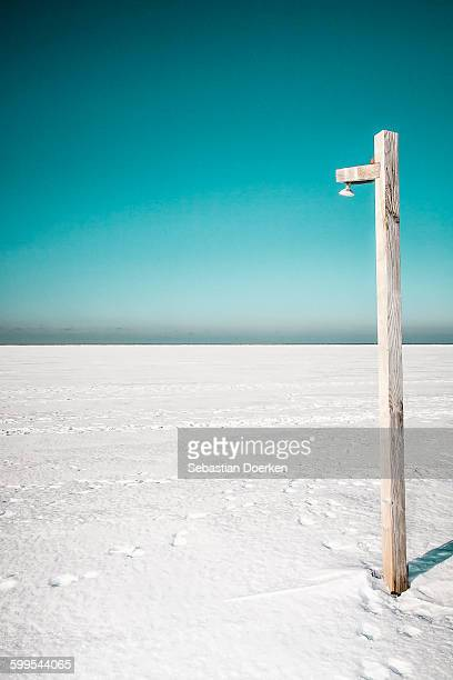 Wooden post on snowy landscape against clear sky